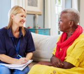 caregiver writing a report with a senior woman