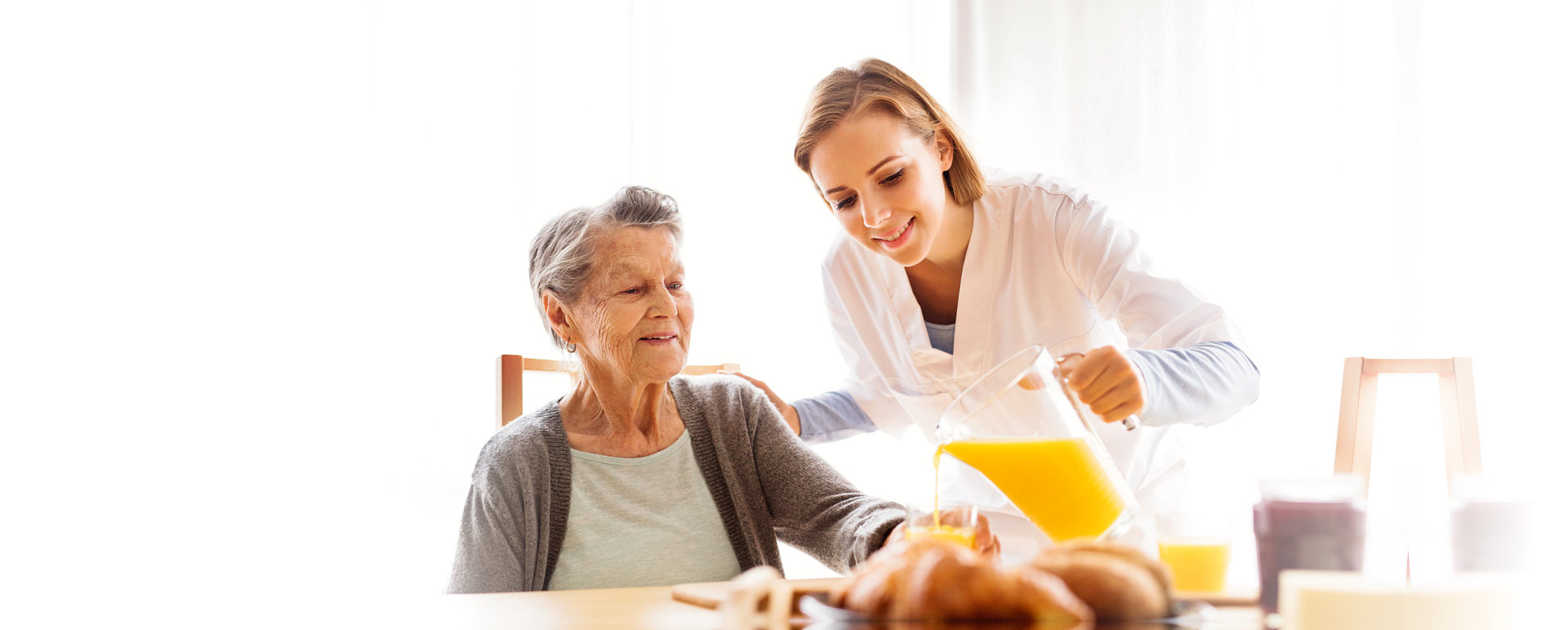 caregiver giving a drink to a senior woman