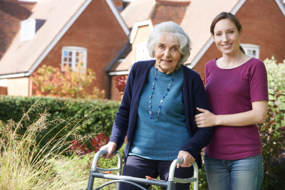 caregiver helping senior woman to use walking frame