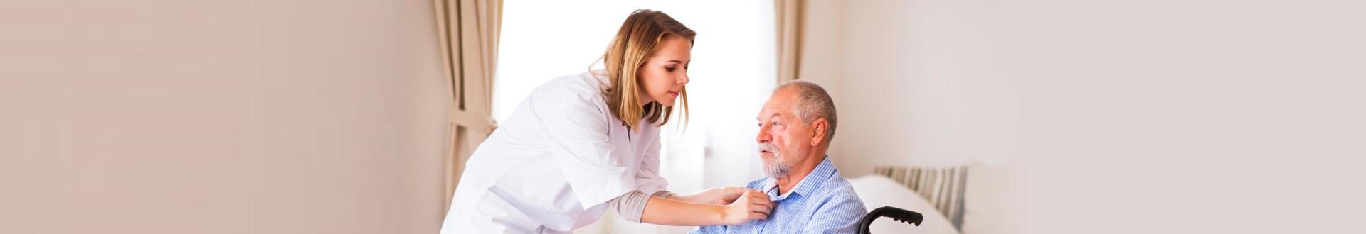 caregiver fixing senior man's clothes